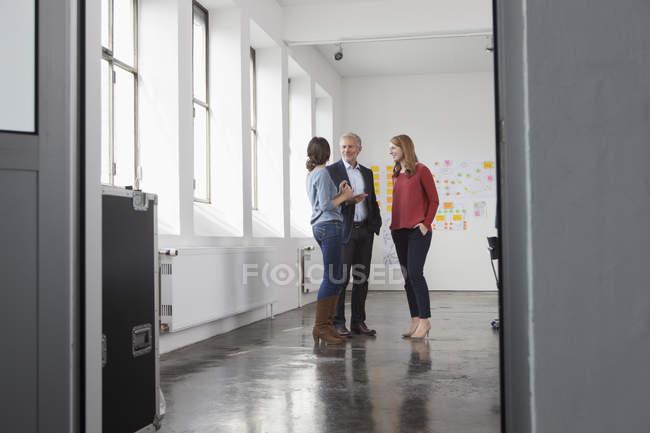 Бизнесмен и две женщины в офис говорить — стоковое фото
