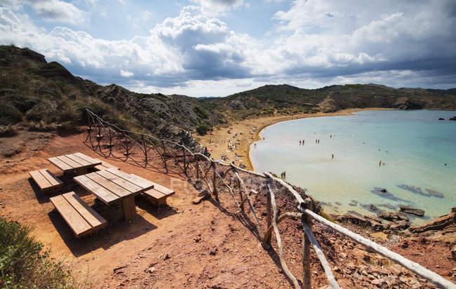Spagna, Isole Baleari, Spiaggia di Caballeria e punto di osservazione con tavoli e panche in legno — Foto stock