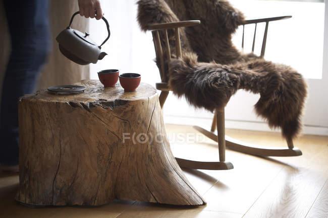 Taças de chá derramamento de mulher mão em chá em uma sala individual — Fotografia de Stock
