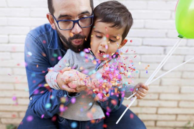 Père et son petit fils soufflant des confettis — Photo de stock