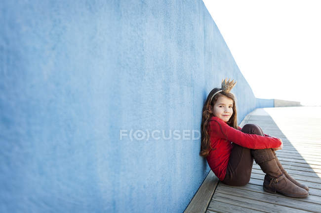 Portrait of little girl with a crown leaning against blue wall — Stock Photo