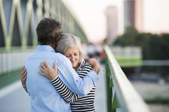 Senior couple embracing on a bridge — Stock Photo