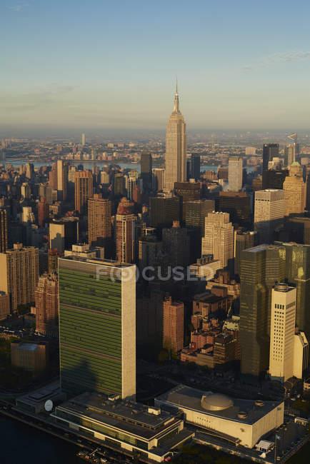 Stati Uniti d'America, dello stato di New York, New York City, quartiere di affari al mattino, Empire State building e le Nazioni Unite edificio in basso a sinistra, vista di paesaggio urbano al tramonto — Foto stock