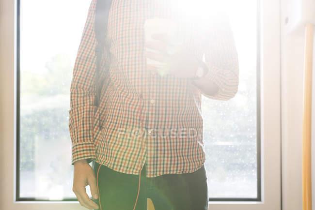 Молода людина з кави, щоб йти стоять біля підсвічування, частковим видом — стокове фото