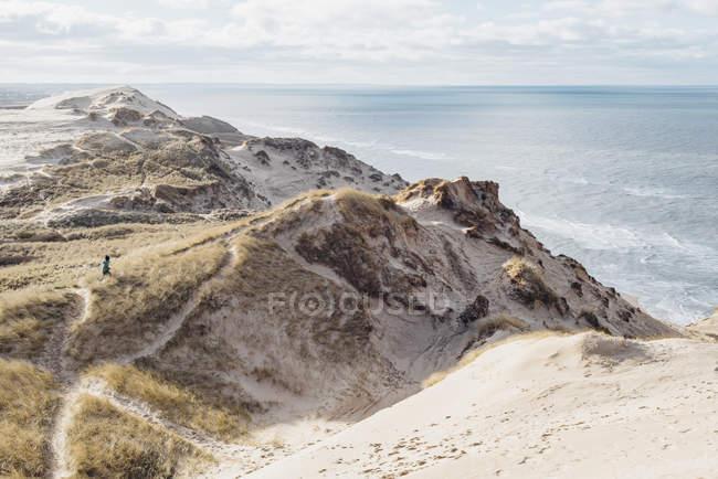 Danimarca, Jutland settentrionale. Ragazzo in esecuzione sulla costa rocciosa ripida — Foto stock