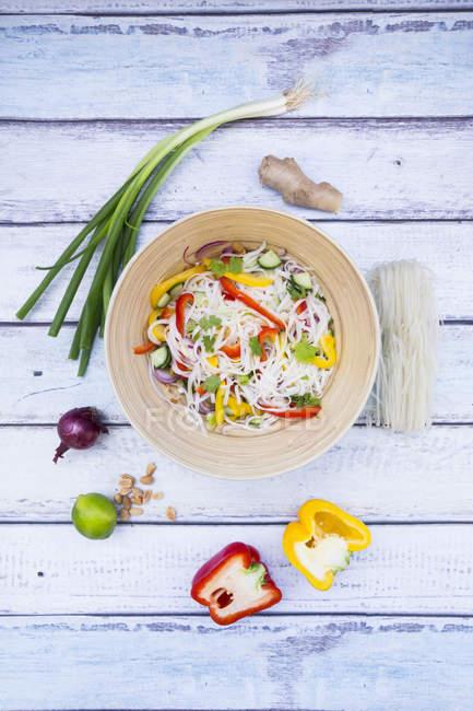 Чаша стекла лапши Салат с овощами и ингредиентов на белое дерево — стоковое фото