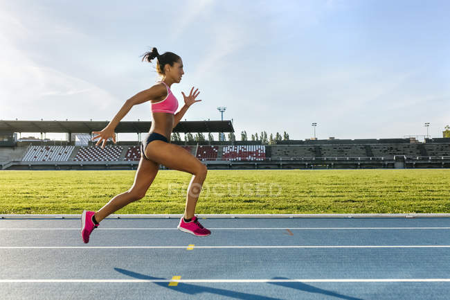 Боковой вид женщины-спринтера, бегущей по беговой дорожке — стоковое фото