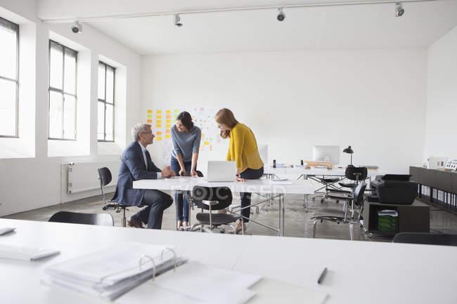 Hombre de negocios y dos mujeres en una reunión de oficina - foto de stock