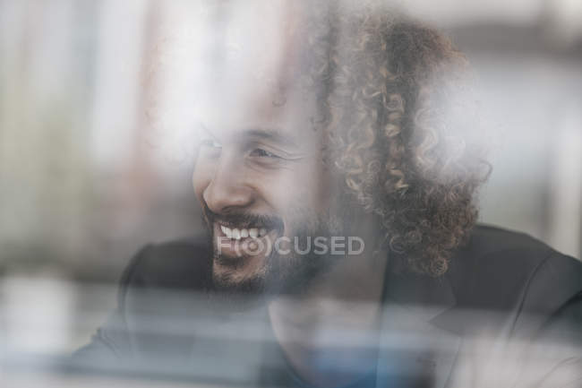 Young man with Afro hairstyle smiling behind glass pane — Stock Photo