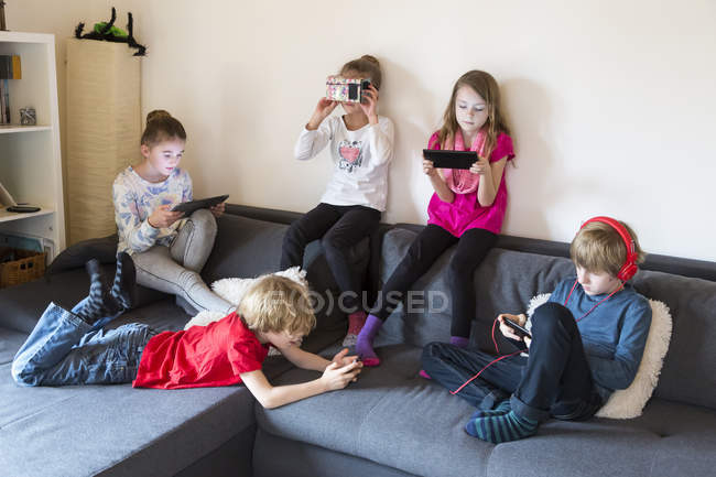 Пять детей на диване с использованием различных цифровых устройств — стоковое фото