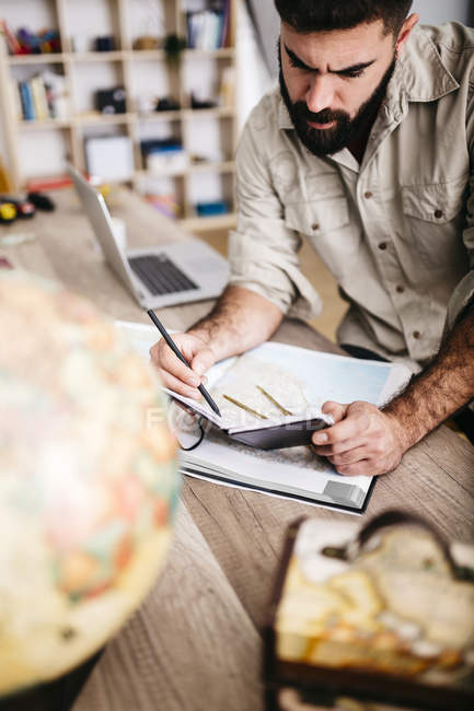 Mann, die Planung der Reise von zu Hause mit Karte und notebook — Stockfoto