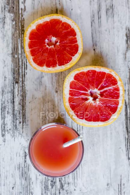 Tranches de pamplemousse et verre de jus de pamplemousse sur bois — Photo de stock