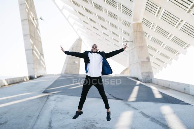 Жизненно важный бизнесмен прыгает под солнечную панель — стоковое фото