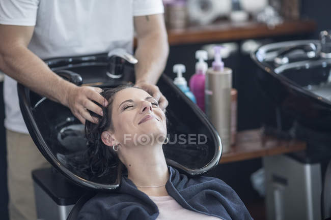 Woman in hair salon getting hair washed — Stock Photo
