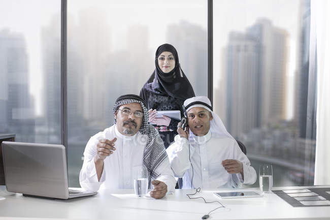 Two Middle Eastern businessmen having a video conference, female assistant in background — Stock Photo