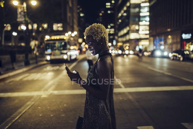 Happy african american woman with cellphone on Times Square at nighttime, NY, USA — Stock Photo