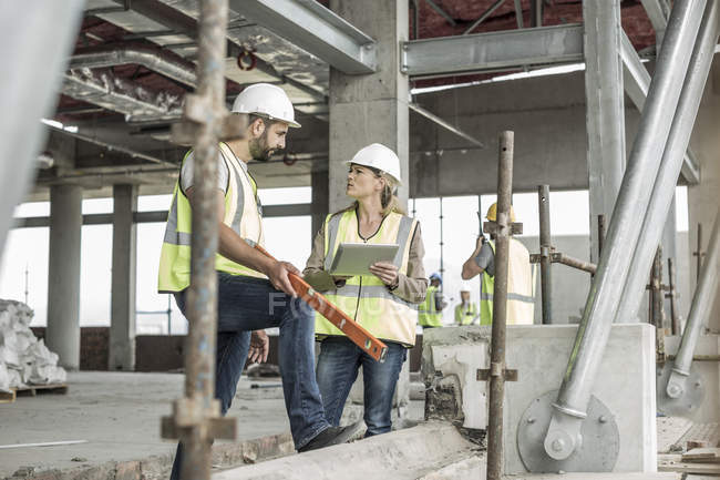 Woman in protective workwear and construction worker discussing in construction site — Stock Photo