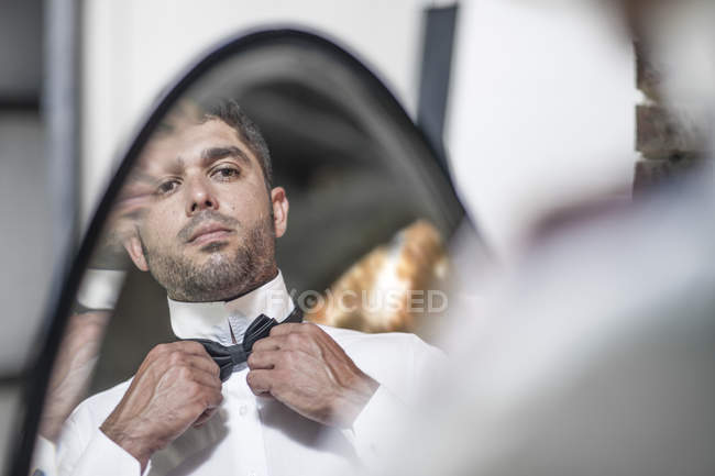 man looking in mirror and adjusting bow tie close up bow tie