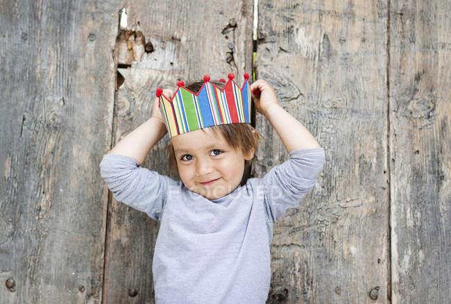 Portrait of smiling little boy wearing paper crown — Stock Photo