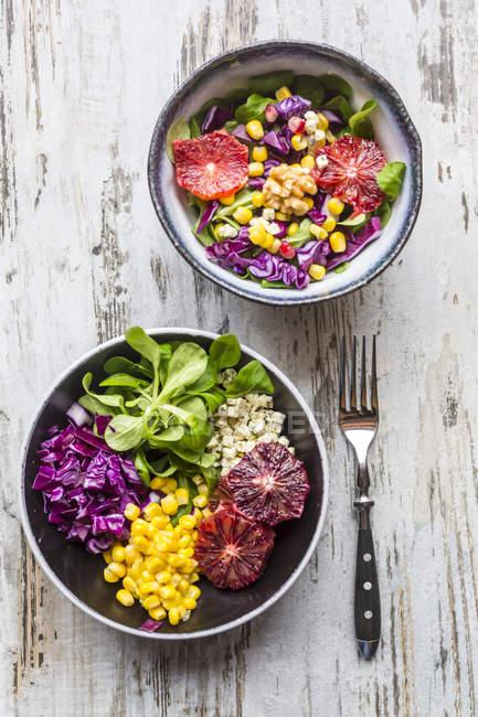 Salate mit Salat, Rotkohl, Mais, Feta-Käse, Blutorange, Walnüssen und Granatapfelkernen — Stockfoto