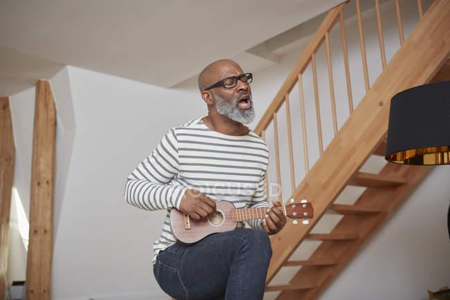 Man singing while playing ukulele — Stock Photo