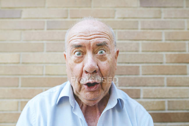 Portrait of senior man pulling funny faces — Stock Photo