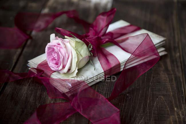 Stapel alter Liebesbriefe und Rosenblüten mit roter Schleife gebunden — Stockfoto