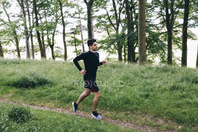 Красивый кавказский спортсмен бегает в парке — стоковое фото