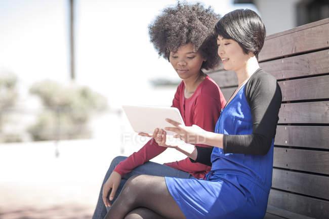 Две молодые женщины сидят на скамейке и смотрят на цифровой планшет — стоковое фото