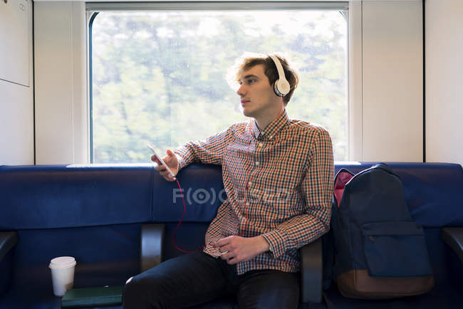 Young man sitting in a train listening music with headphones — Stock Photo