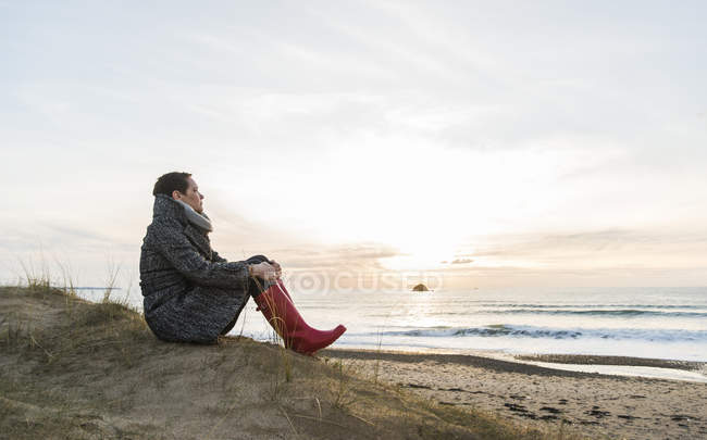 Woman sitting at the coast and looking at view, France, Bretagne, Finistere, Crozon peninsula — Stock Photo