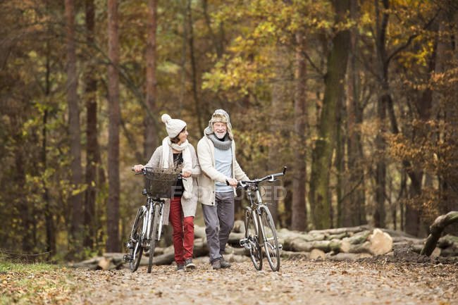 Senior couple with bicycles in autumnal wood — Stock Photo