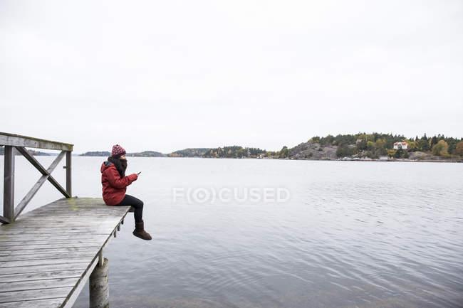 Donna che si siede sul molo di messaggi di testo — Foto stock