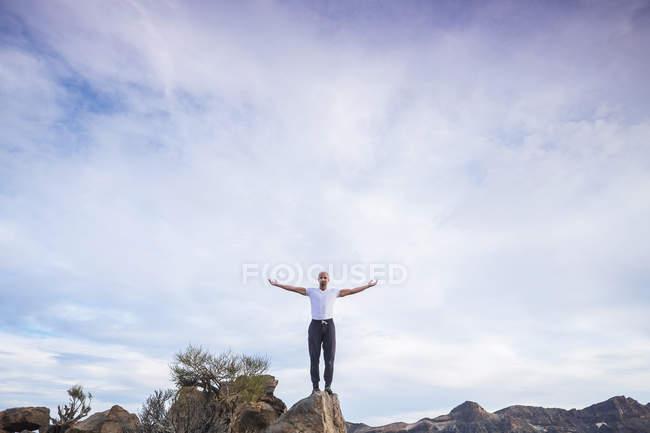 Spanien, Teneriffa, Mann mit ausgestreckten Armen auf einem Felsen — Stockfoto