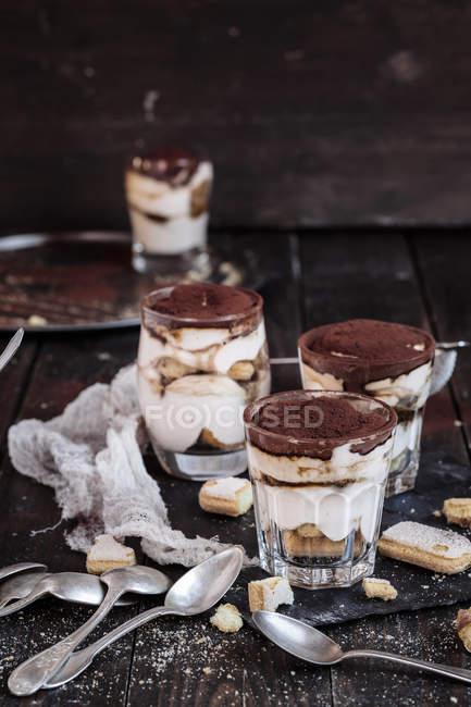 Vista de cerca de copas de tiramisú con galletas y cucharas - foto de stock