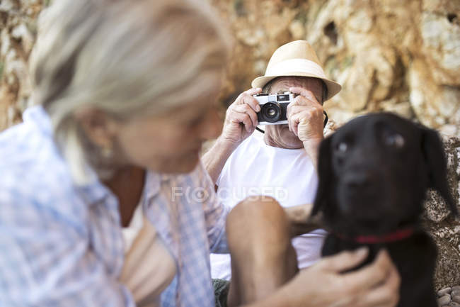 Active cute senior couple, man taking photo of woman with dog — Stock Photo