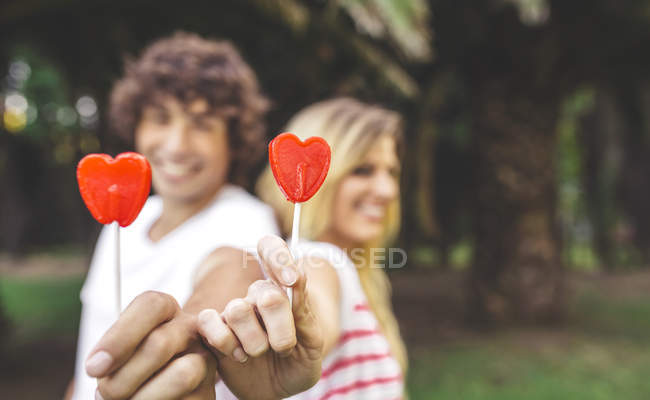 Young couple holding heart-shaped lollipops — Stock Photo