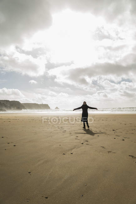 Woman standing on the beach with outstretched arms, France, Bretagne, Finistere, Crozon peninsula — Stock Photo