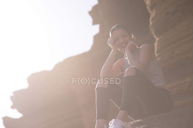 Young woman sitting in front of a rock face at backlight — Stock Photo