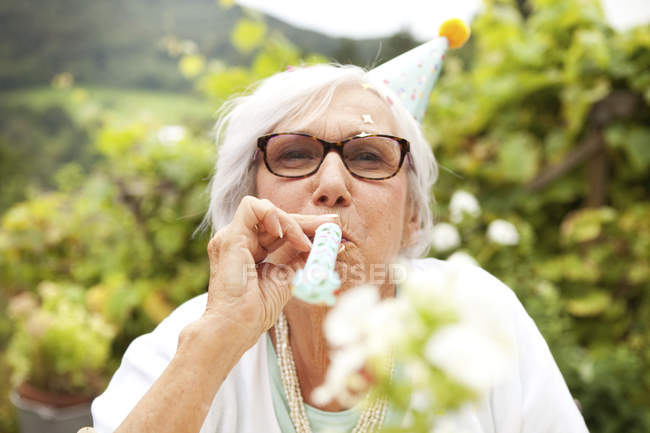 Senior woman blowing party blower at garden — Stock Photo
