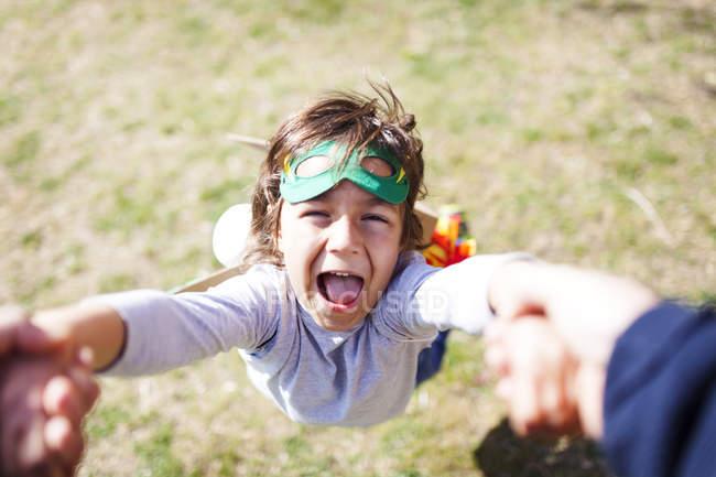 Retrato de niño vestido como un superhéroe jugando con el padre en un prado - foto de stock
