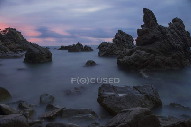 Spain, Costa Brava, Lloret de Mar, rock formations at Cala dels Frares by sunset — Stock Photo