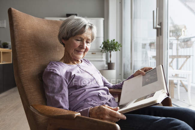 Portrait of senior woman sitting on armchair at home watching photo album — Stock Photo