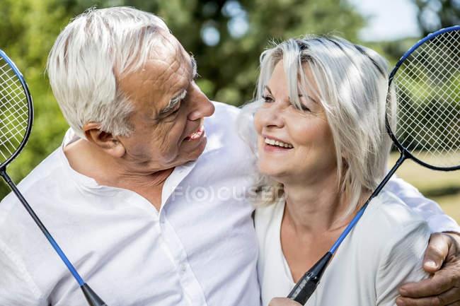 Усміхаючись немолода пара проведення бадмінтон на відкритому повітрі — стокове фото