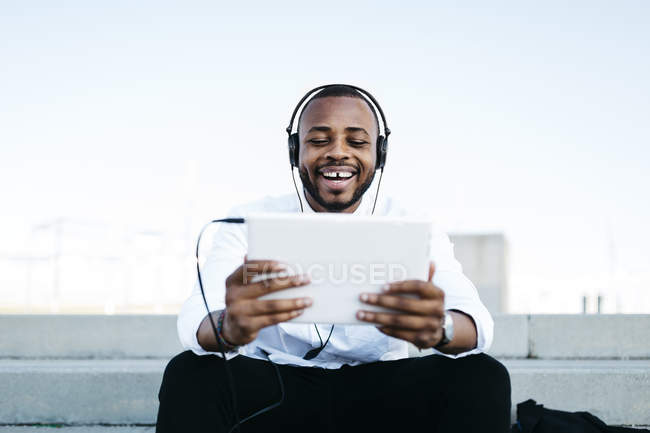 Happy man sitting on stairs wearing headphones and holding tablet — Stock Photo