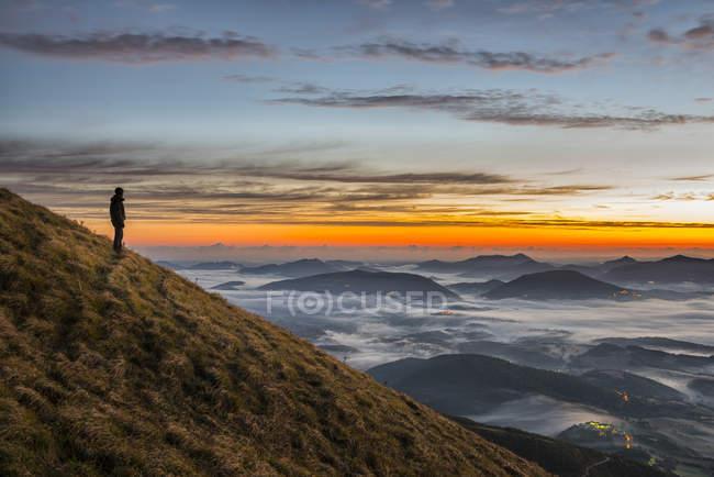 Italia, Umbría, Apeninos, excursionista de pie en Monte Acuto observando amanecer - foto de stock