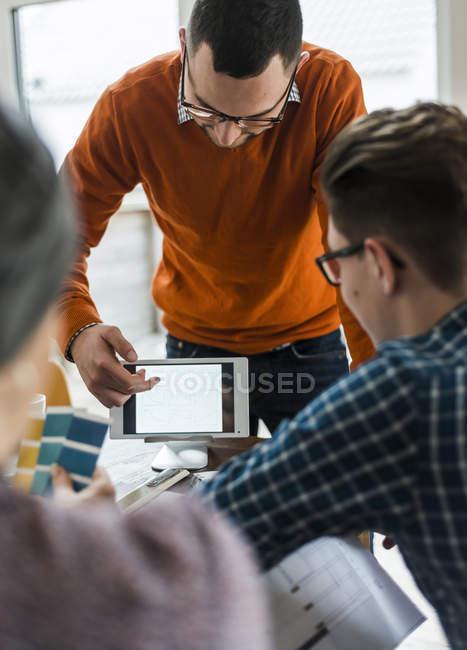 Colegas no escritório olhando para tablet digital mostrando diferentes formas — Fotografia de Stock