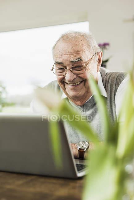 Portrait de l'heureux homme senior avec ordinateur portable à la maison — Photo de stock