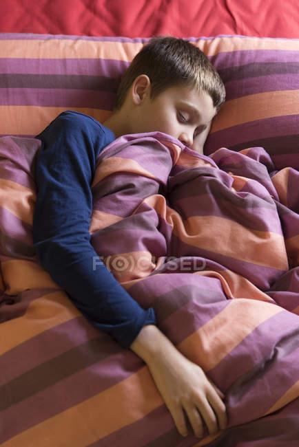 Rapaz dormindo na cama com cobertor listrado — Fotografia de Stock