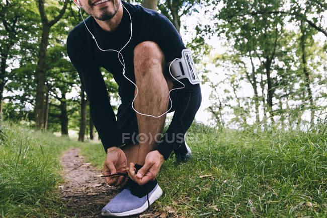 Обрезанный образ красивого кавказского спортсмена, завязывающего шнурки — стоковое фото